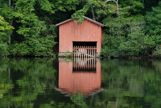 Boat house on water reflection
