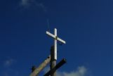 A cross on a telephone pole with a CB Antenna on top.