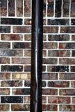 A pole going verical against a brick wall