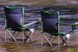 Two folding chairs in water